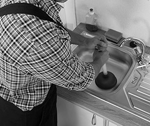 Image of a man plumbing a sink.