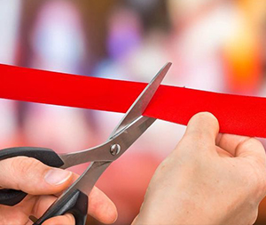 Image of a ribbon being cut with scissors.