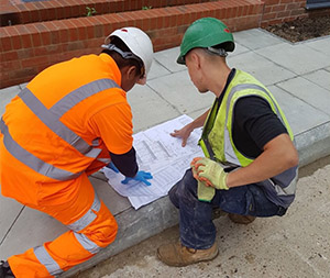 Image of two engineers reading a drainage plan.